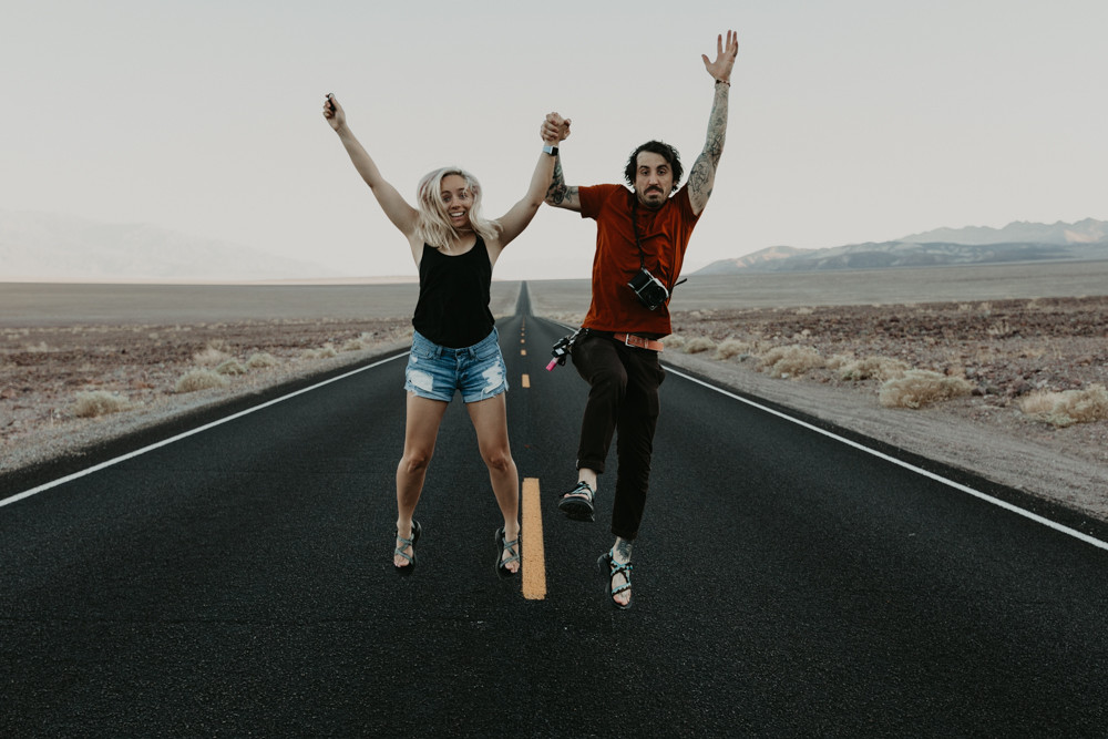 man and woman holding hands and jumping in the air in the middle of a long and straight black road in the desert in death valley national park, captured by las vegas elopement photographer hayway films