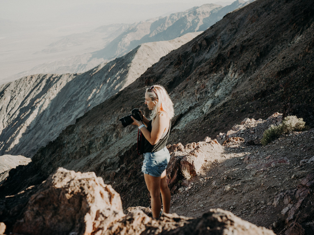 woman stands on a mountain side holding a camera in death valley national park