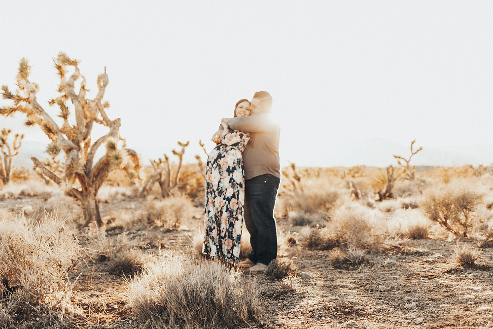 A couple stands together in joshua tree national park white woman wears long floral dress during sunset. Captured by las vegas engagement photographer hayway films
