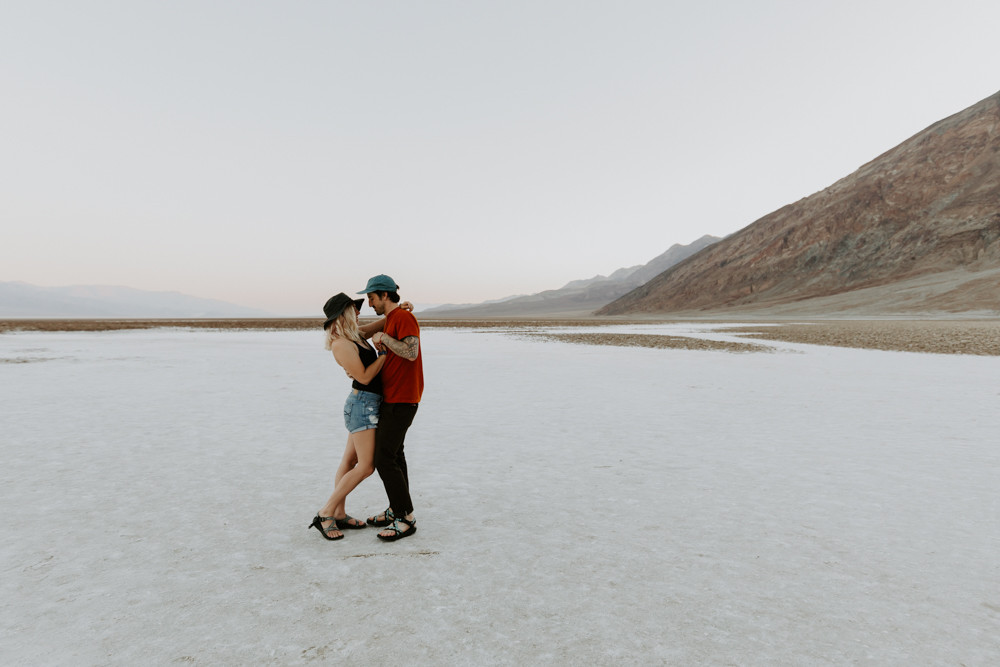 badwater basin adventurous engagement pictures by las vegas elopement photographer hayway films, man and woman hold hands and walk away from camera, wearing matching chacos sandals.