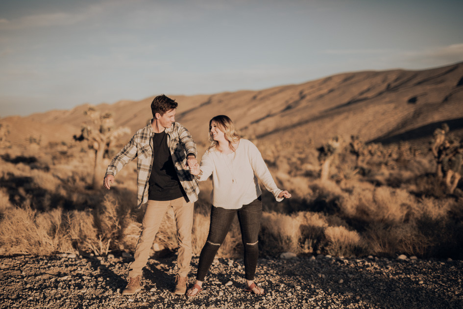 Beautiful couple hugging and kissing in the desert at sunset, captured by las vegas wedding photographer hayway films. Adventurous engagement photography in Joshua Tree National Park.