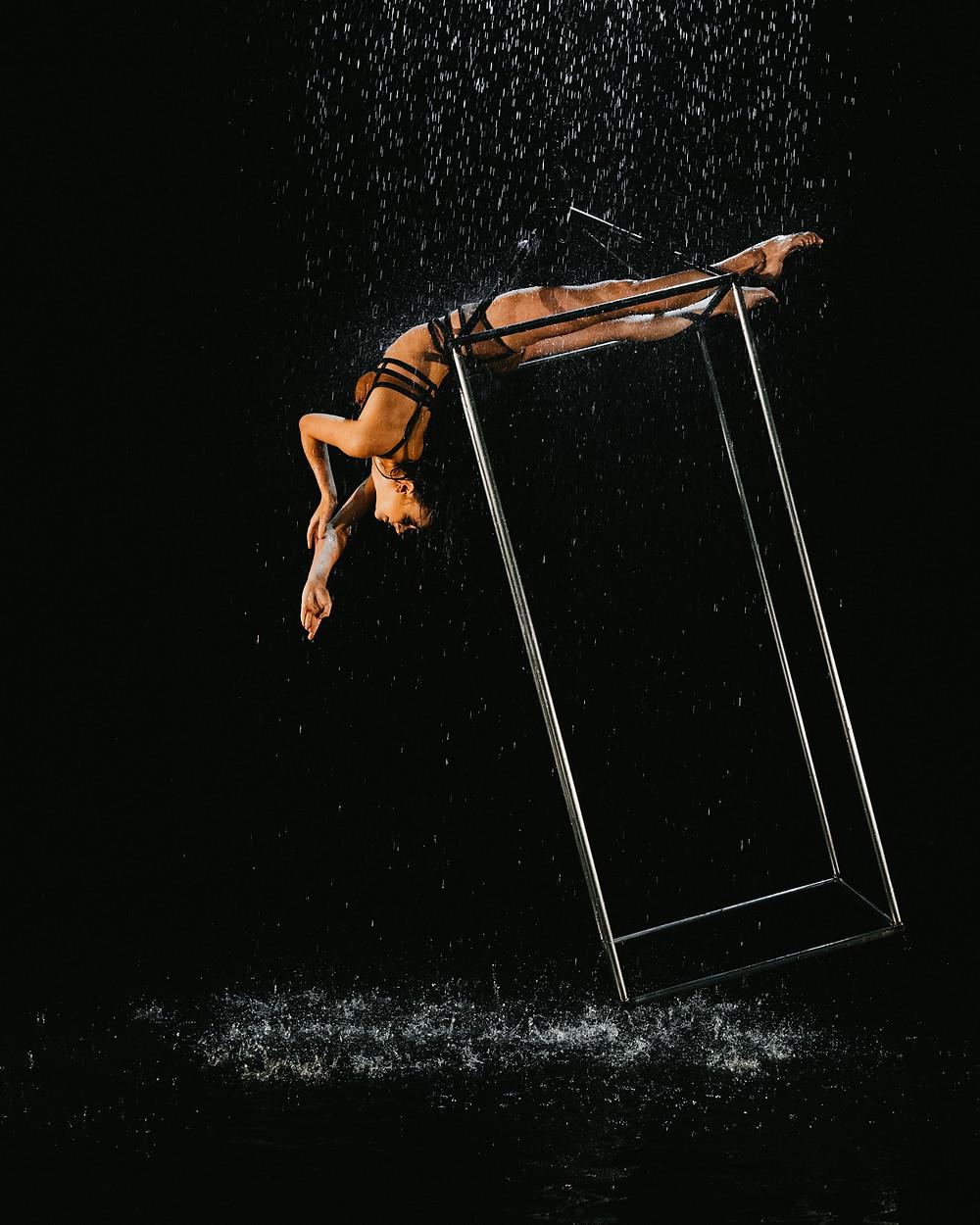 circus performer in Las Vegas hangs upside down in the rain, captured by las Vegas wedding photographer hayway films