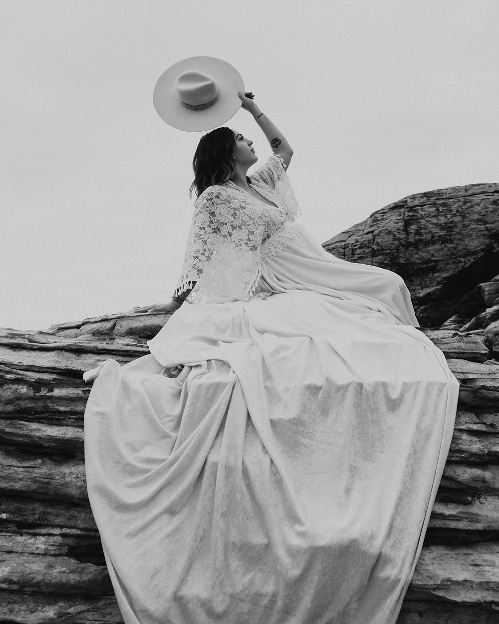 Black and white image of woman sitting on a mountain wearing a long white lace dress and holding her brimmed boho hat in the air. Maternity pictures at valley of fire captures by las vegas wedding photographer hayway films.