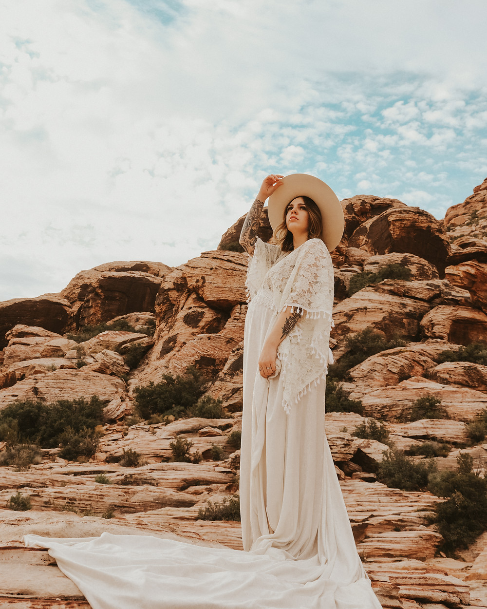 Pregnant woman with tattoos stands on top of a mountain wearing a long white lace boho dress. Maternity pictures at valley of fire captures by las vegas wedding photographer hayway films.