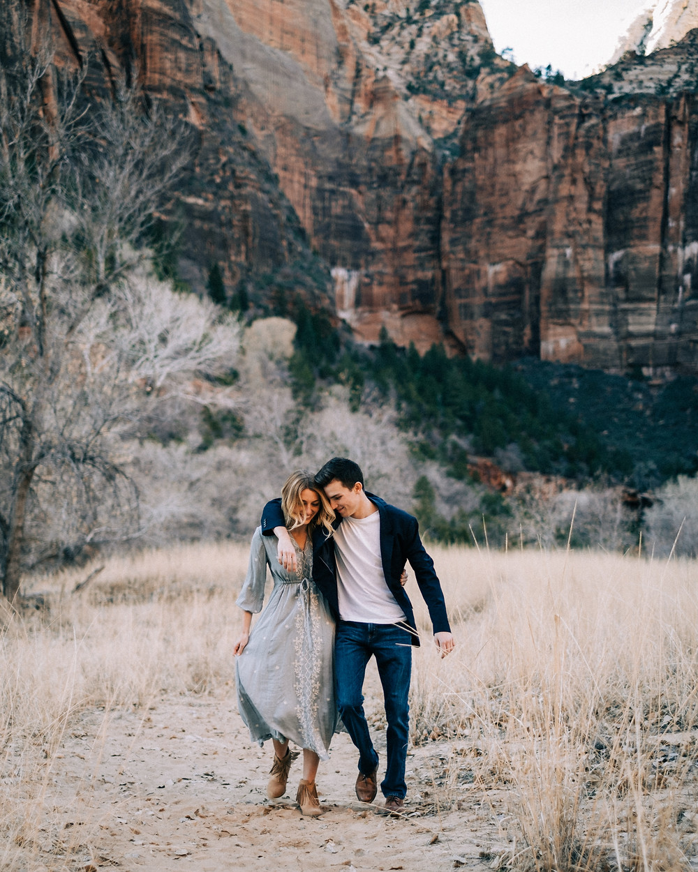 gorgeous engaged couple captured snuggling at their zion national park engagement session by zion elopement photographer hayway films