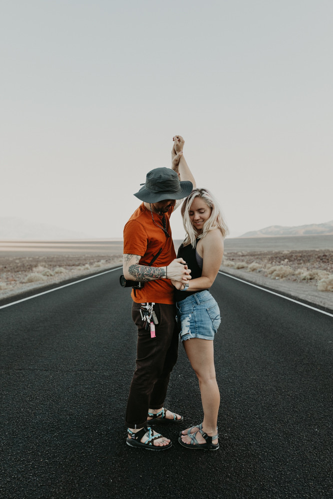 man and woman holding hands in the middle of a long and straight black road in the desert in death valley national park, captured by las vegas elopement photographer hayway films