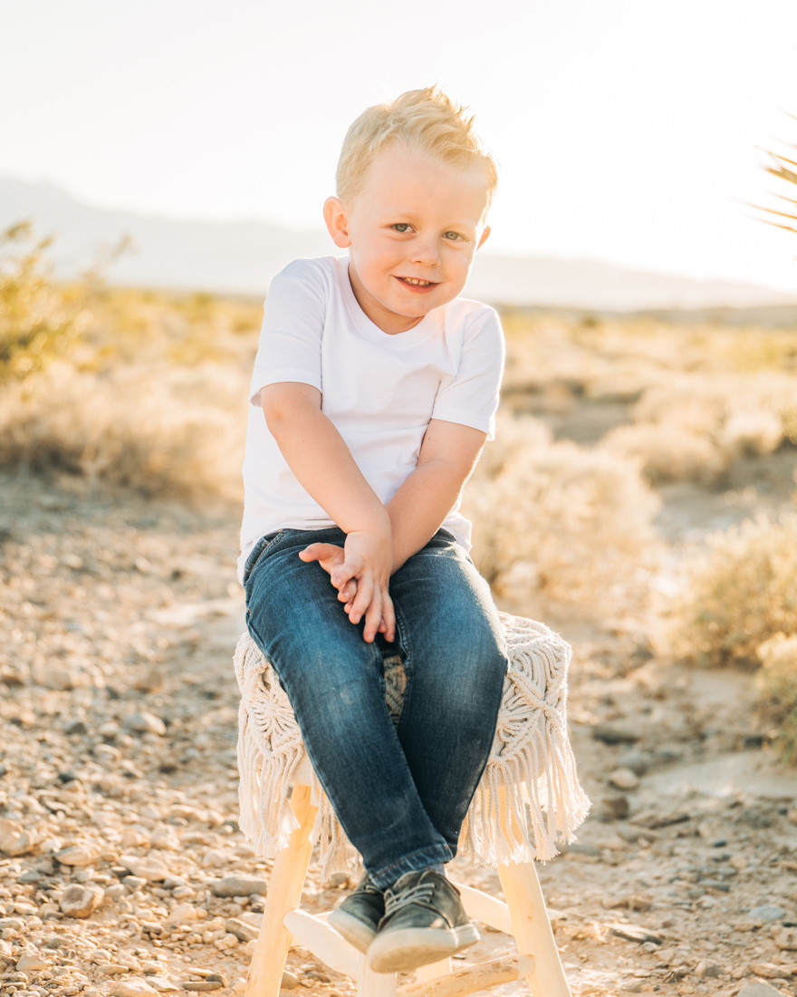 Little boy sitting on a chair in the desert, smiling, Little girl with pigtails in a pink tutu, posing with her brother, captured by las vegas family photographer in tule springs fossil beds