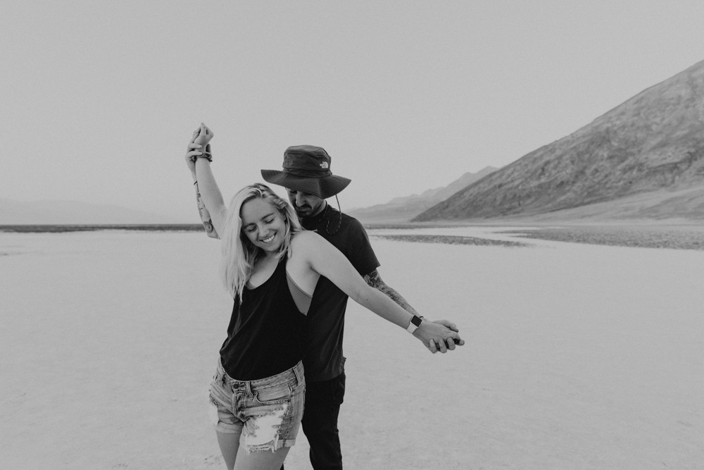 badwater basin adventurous engagement pictures by las vegas elopement photographer hayway films, man and woman hold hands and walk away from camera, wearing matching chacos sandals. black and white photograph