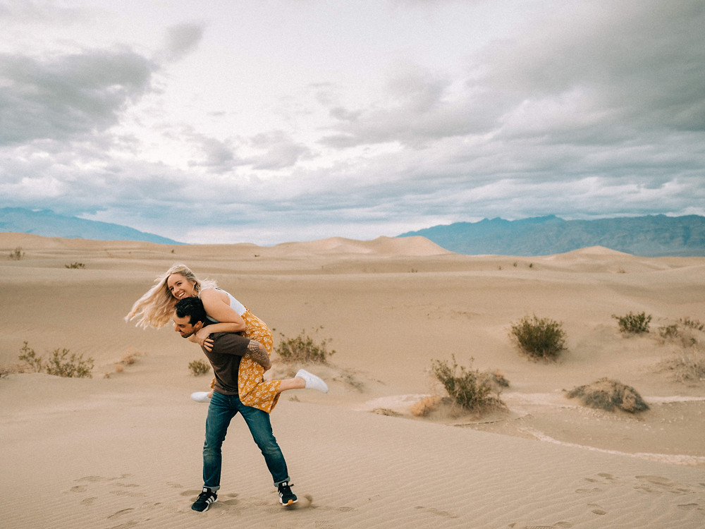 Man and woman giving a piggy back ride and smiling. Death valley sand dunes engagement photos. Captured at sunset by las vegas wedding photographer hayway films. Mesquite flats elopement.