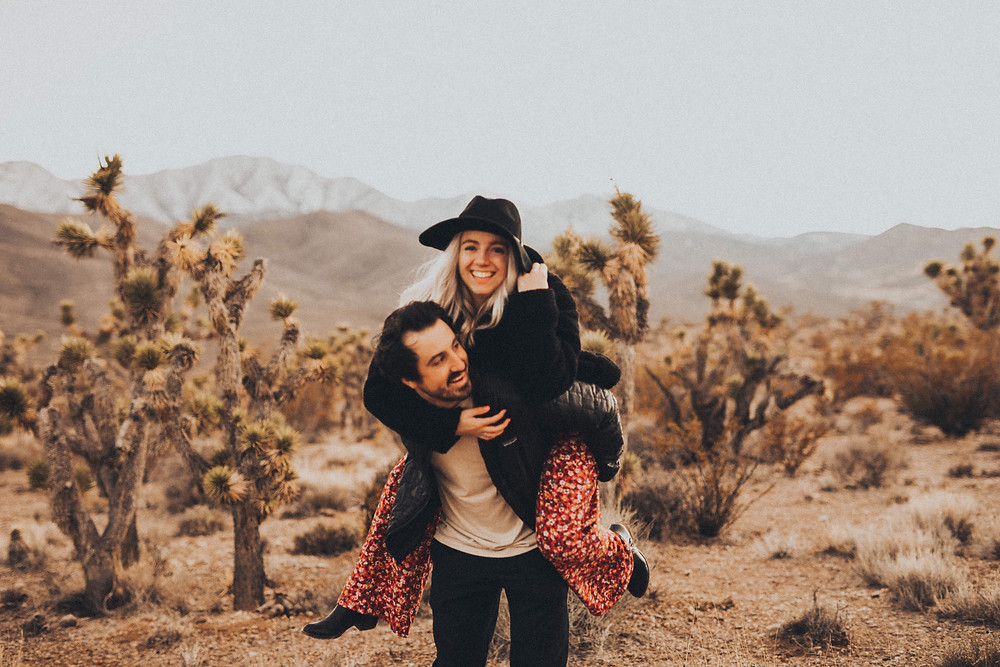 Man gives woman a piggyback ride in the desert surrounded by joshua trees. The golden desert with snowy mountains captured by las vegas engagement photographer hayway films.