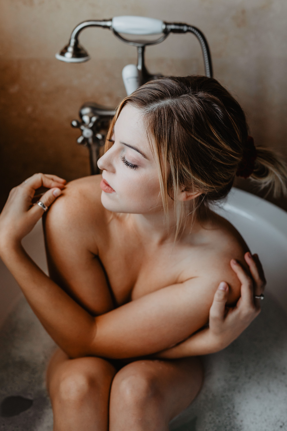 Nude woman posing in the bubble bath, taken by las vegas boudoir photographer haway films