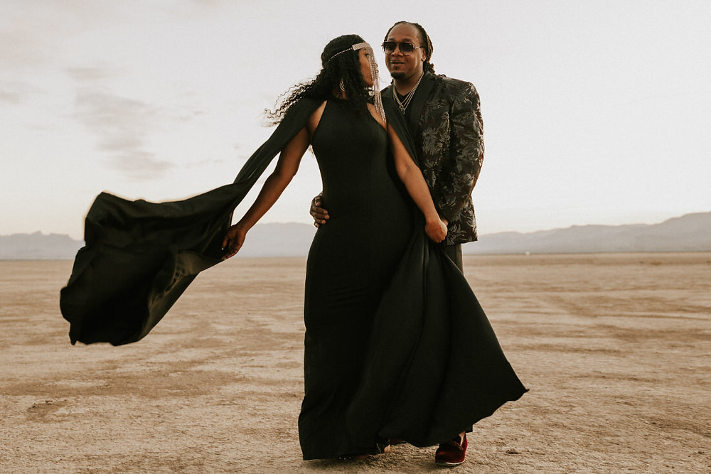 Bride and groom pose in the desert outside of Las Vegas for their intimate elopement. Captured by Las Vegas wedding videographers brazen honey films, bride wears an all black wedding dress.