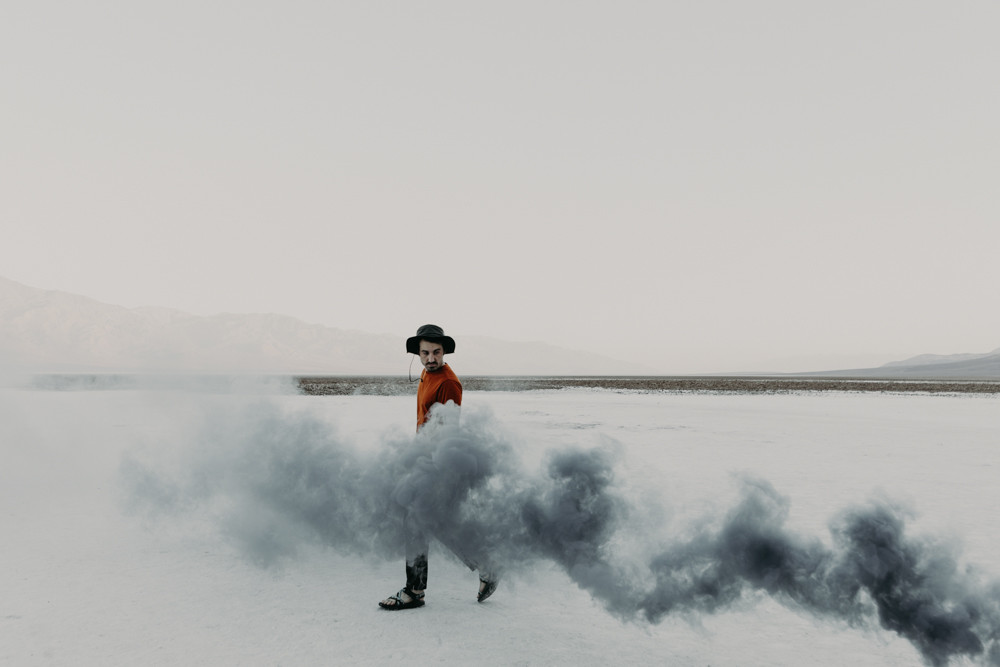 man walks behind a grey smoke bomb at badwater basin in death valley national park.