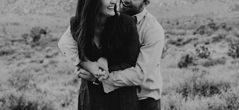 Black and white photo of man and woman hugging and laughing. Red Rock canyon engagement pictures in the snow. Captured by las vegas wedding photographer hayway films.