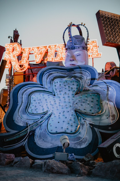 Blue four leaf clover vintage neon sign with glowing riveria twinkling lights sing Neon Boneyard in Las Vegas Nevada, colorful vintage neon signs arranged, captured by las vegas elopement photographer hayway films.