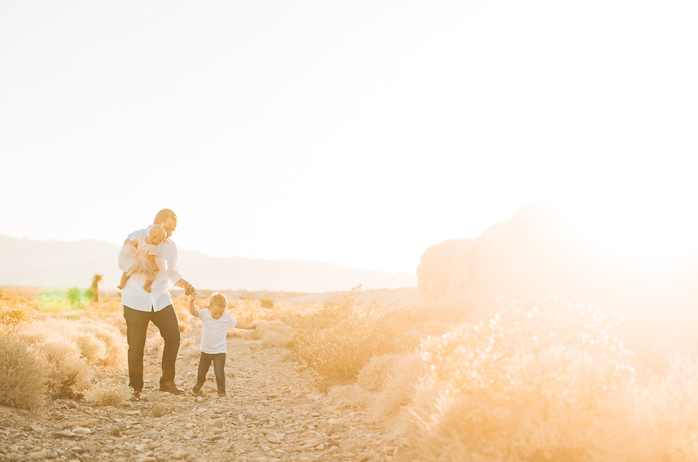 A father holding his little girl, walking with his son, captured by las vegas family photographer in tule springs fossil beds