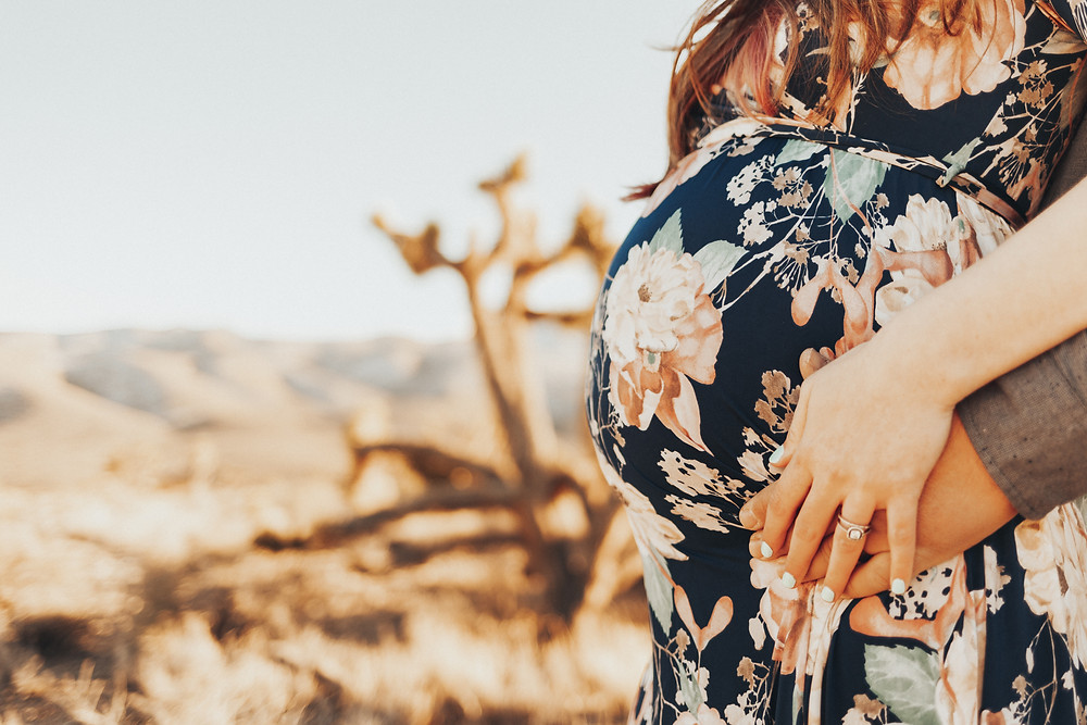 A womans pregnant belly covered by a blue and pink floral dress white her husband holds her hands, captured in the desert by las vegas maternity photographer hayway films