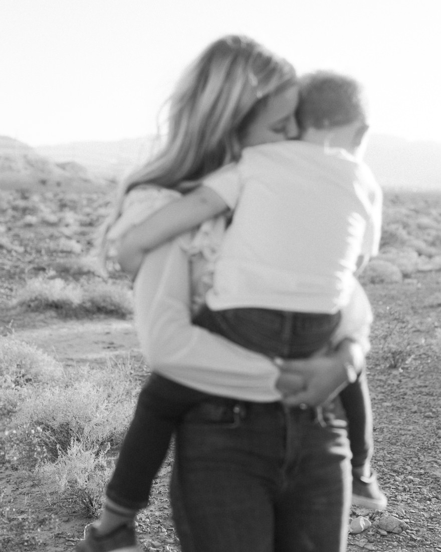 Black and white photograph of mom holding and kissing her little boy, Little girl with pigtails in a pink tutu, posing with her brother, captured by las vegas family photographer in tule springs fossil beds