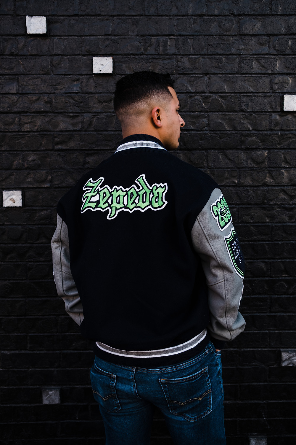 High school senior boy wears his letterman jacket in downtown las vegas for vibrant las vegas senior portraits in front of colorful mural walls