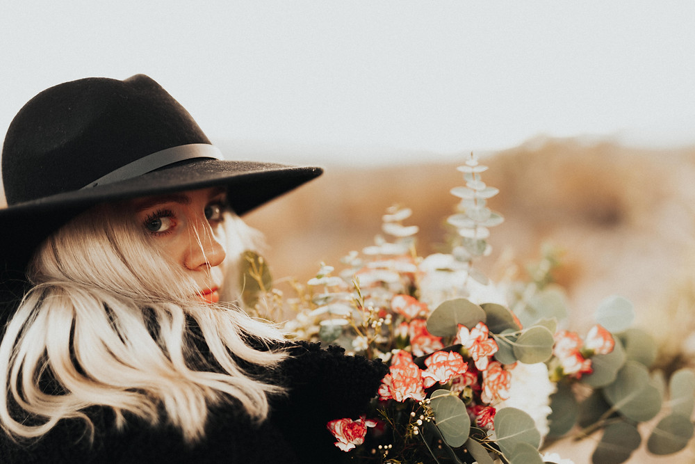 Blonde woman wearing a black hat holds a bouquet of flowers and turns to look at the camera Man gives woman a piggyback ride in the desert surrounded by joshua trees. The golden desert with snowy mountains captured by las vegas engagement photographer hayway films.