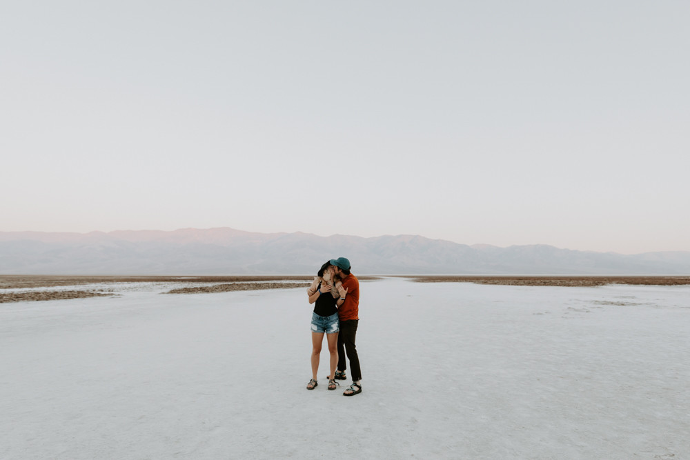 badwater basin adventurous engagement pictures by las vegas elopement photographer hayway films, man and woman hugging and kissing, wearing matching chacos sandals.