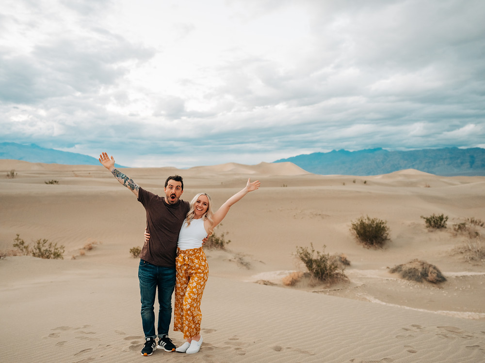 Man and woman hugging with their arms in the air. Death valley sand dunes engagement photos. Captured at sunset by las vegas wedding photographer hayway films.