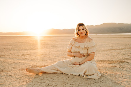 blonde pregnant mother holds her belly and poses for boho maternity pictures at sunset captured by las vegas maternity photographer hayway films.