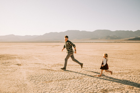 Dad and daughter run around in the desert at sunset captured by las vegas family photographer hayway films