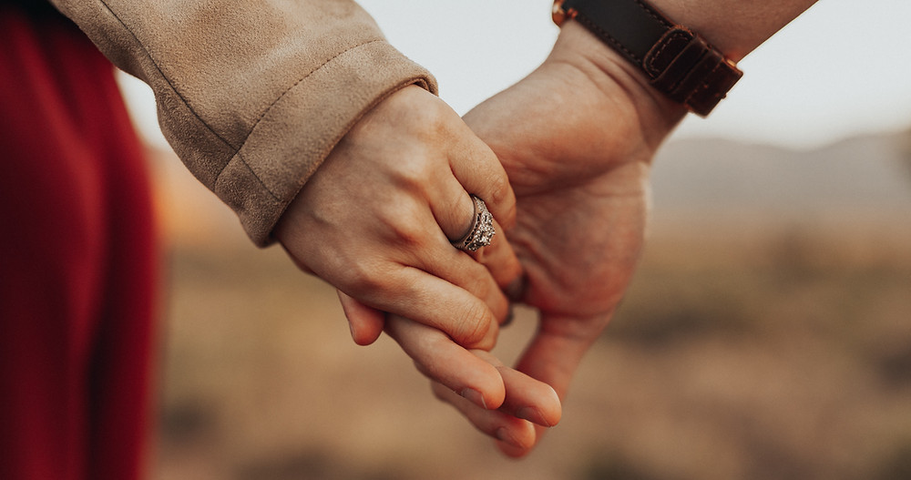 man and woman hold hands in the desert, beautiful engagement ring with diamonds