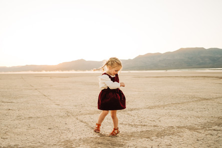 little girl with pigtail braids does a spin for the camera at the dry lake bed in las vegas by las vegas photographer hayway films