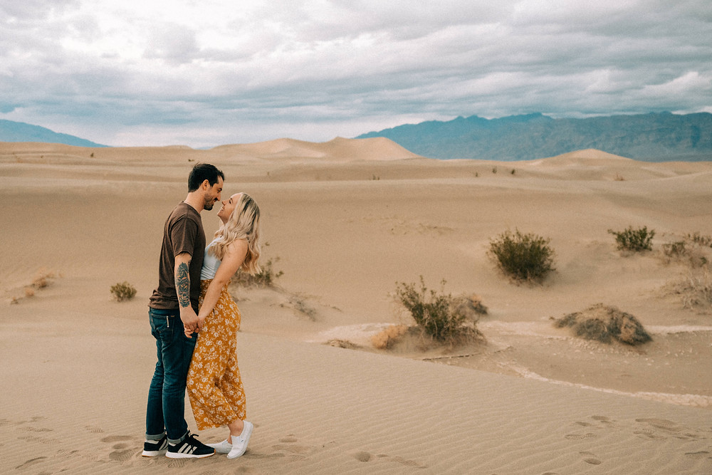 Man and woman holding hands and smiling at each other. Death valley sand dunes engagement photos. Captured at sunset by las vegas wedding photographer hayway films.