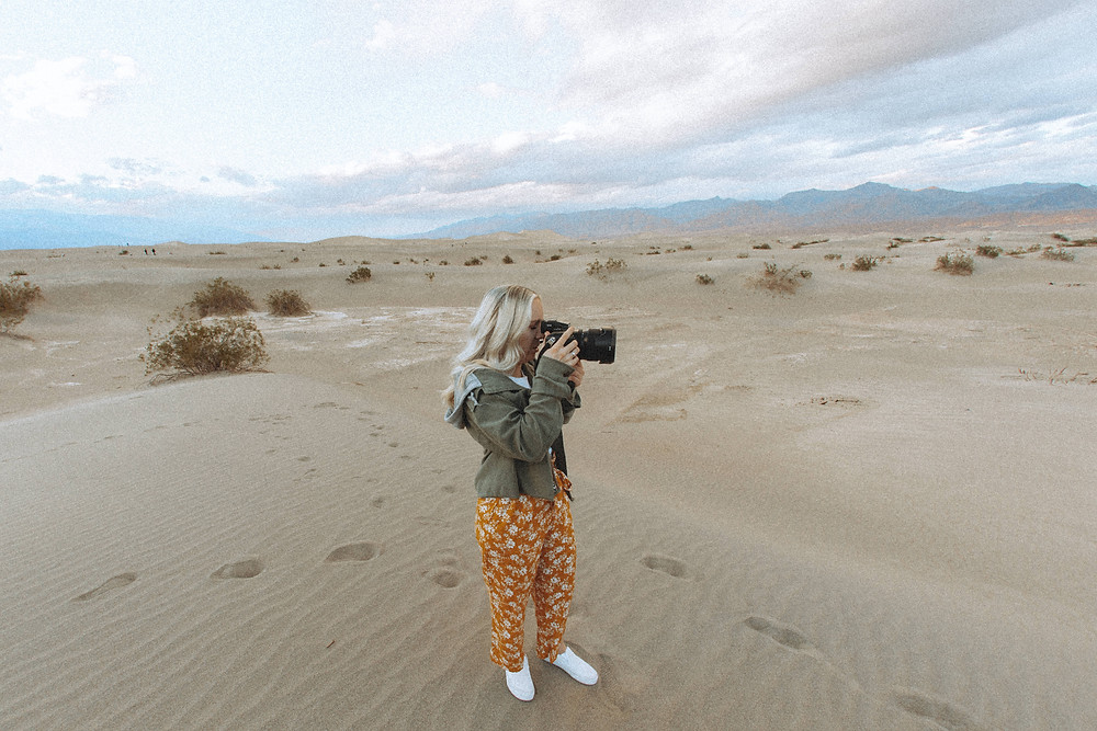 Blonde woman holds camera and takes a picture of mesquite flats sand dunes at death valley national park. Captured by las vegas wedding photographer hayway films.