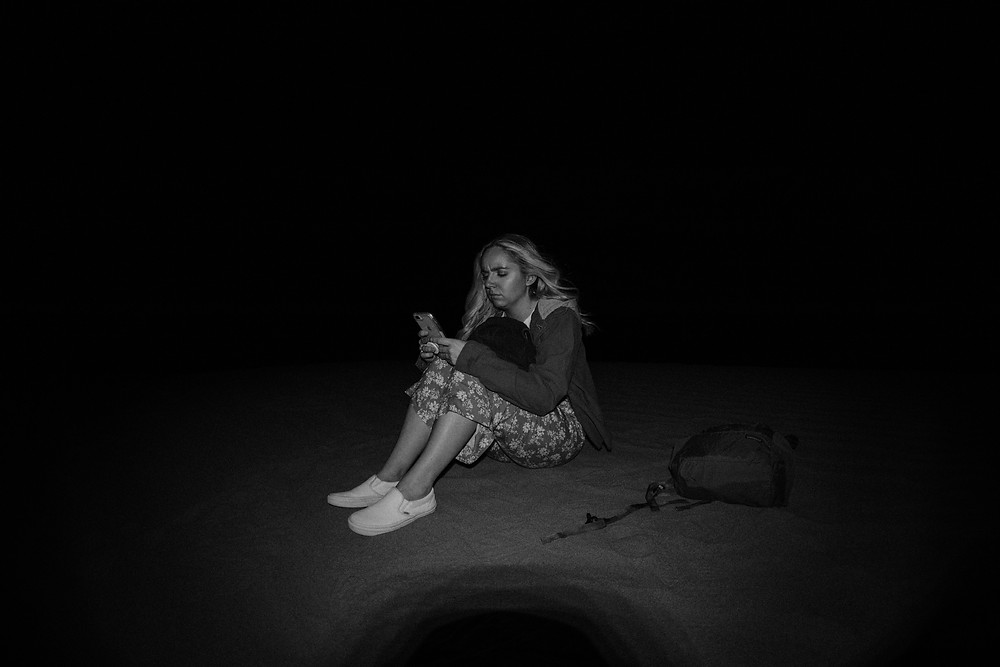 black and white photography of woman sitting in the dark on her phone.