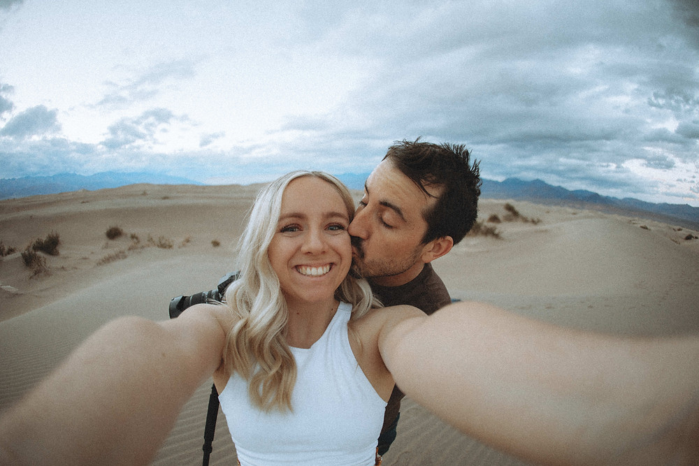 man and woman take selfie at the mesquite flat sand dunes in death valley national park.