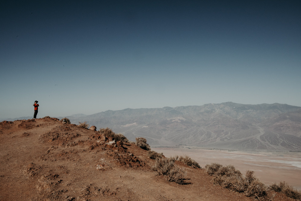 man stands on top of a mountain taking a picture of dantes view in death valley national park