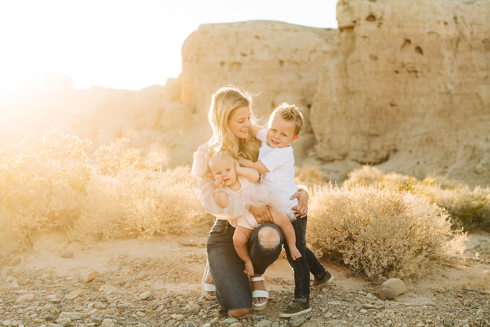 Mom kneeling, holding her two young children, posing for family pictures in the desert, captured by las vegas family photographer in tule springs fossil beds