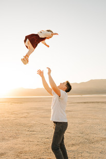 Beautiful sunset portrait of dad throwing little daughter in the air, at the dry lake bed. las vegas family photographer in the desert