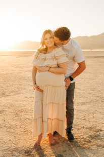 Pregnant woman in cream colored boho dress holds her pregnant belly while her husband holds her and kisses her. Beautiful golden hour maternity portraits captured by las vegas maternity photographer hayway films at the dry lake bed