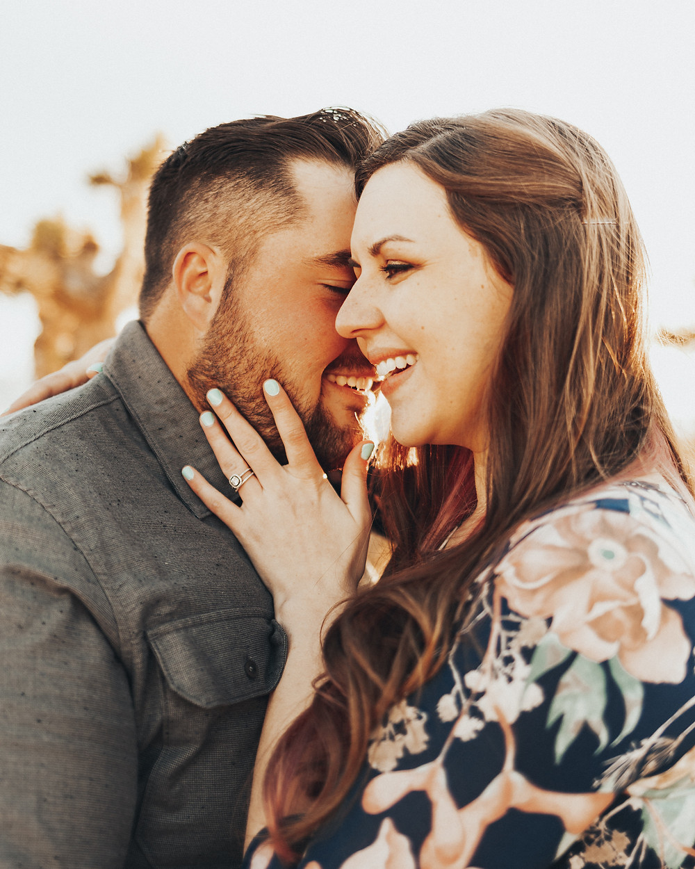 A couple hold each other close and laugh during their las vegas engagement photo shoot
