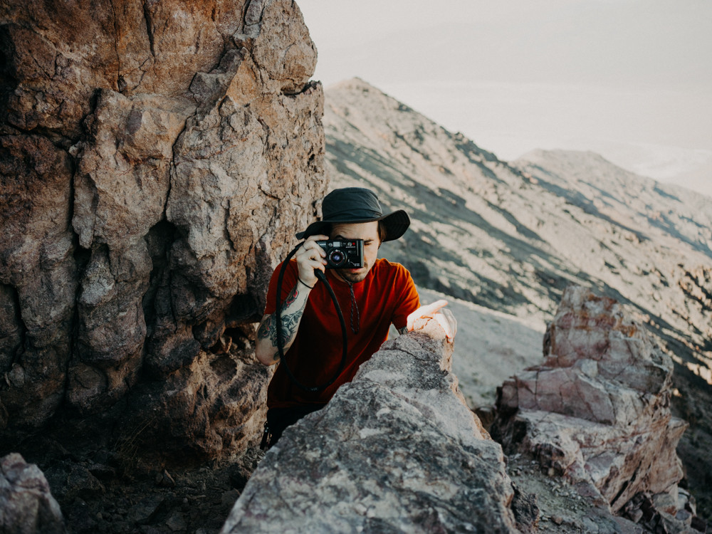 man crouches in the mountains, holding a vintage film camera to his eye in death valley national park.