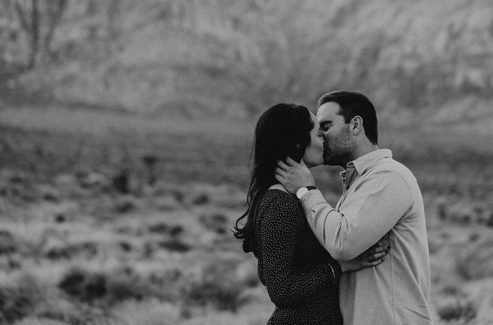 Black and white photo of man and woman kissing in the desert. Red Rock canyon engagement pictures in the snow. Captured by las vegas wedding photographer hayway films.