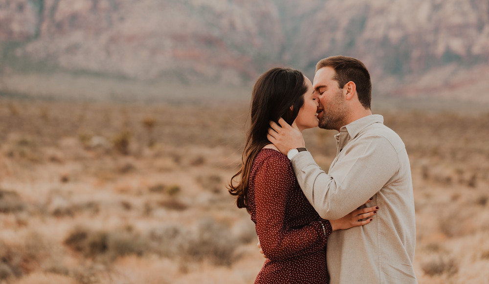 Red Rock canyon engagement pictures in the snow. Captured by las vegas wedding photographer hayway films. Man and woman kissing.