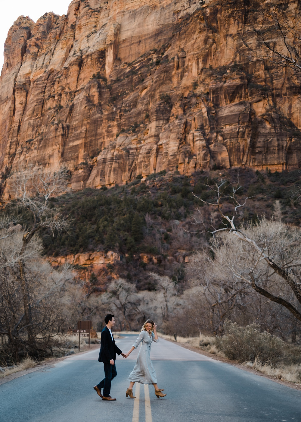Newely engaged couple take beautiful engagement pictures in zion national park with bride wearing beautiful blue dress.