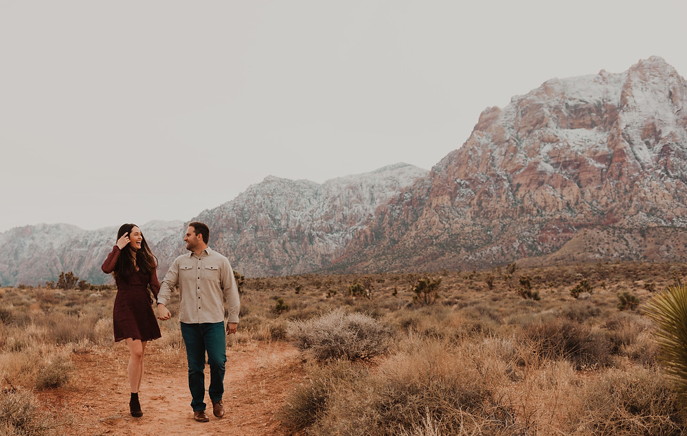 Red Rock canyon engagement portraits in the snow. Captured by las vegas wedding photographer hayway films. Man and woman walk towards the camera holding hands and laughing.