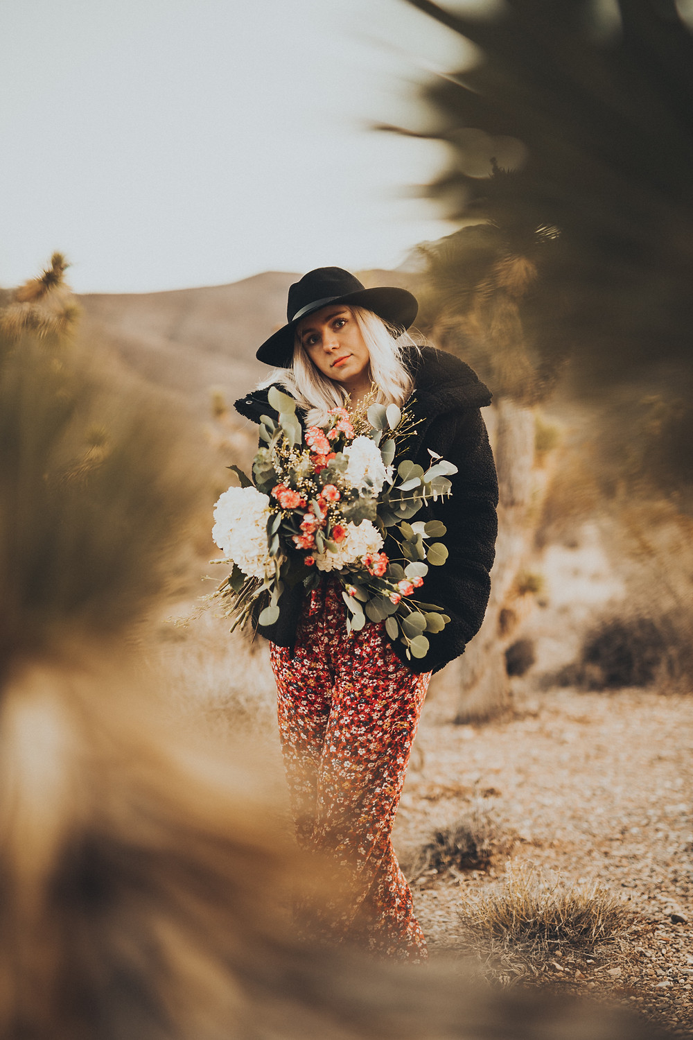 Woman holding a bouquet of flowers and wearing a brimmed hat poses in the desert Man gives woman a piggyback ride in the desert surrounded by joshua trees. The golden desert with snowy mountains captured by las vegas engagement photographer hayway films.