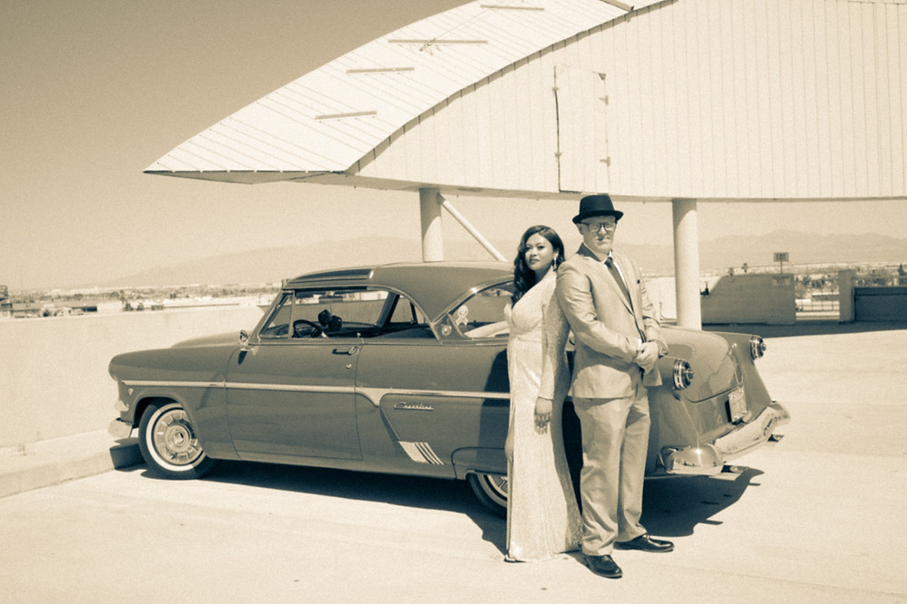 Vintage black and white film photograph of couple on a downtown las vegas rooftop with a 50's vintage car on their wedding day take by las vegas elopement photographer brazen honey films