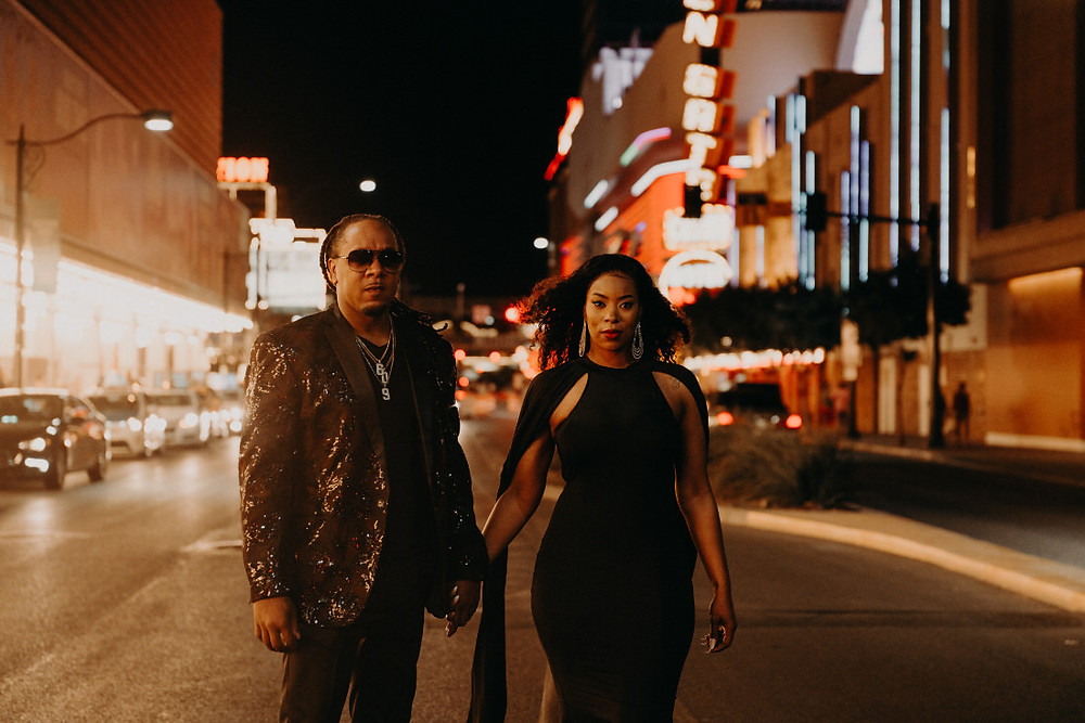 Bride and groom wearing all black wedding outfits, pose holding hands in the middle of the street on Fremont in downtown Las Vegas. Captured by Las Vegas wedding photographer brazen honey films.