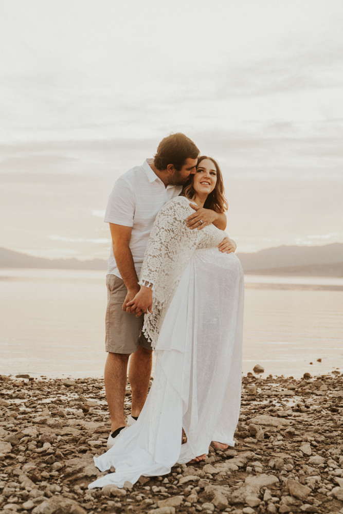 Pregnant mother to be and husband wearing all white hold in embrace at lake mead photographer by las vegas maternity photographer