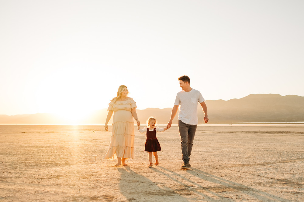 Family holding hands, walking in the desert at sunset, captured by las vegas family photographer hayway films at dry lake bed.