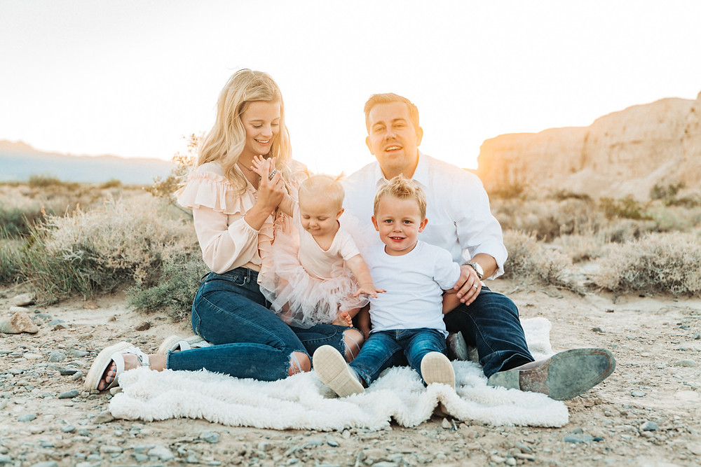 Beautiful family sitting together on a blanket, Little girl with pigtails in a pink tutu, posing with her brother, captured by las vegas family photographer in tule springs fossil beds
